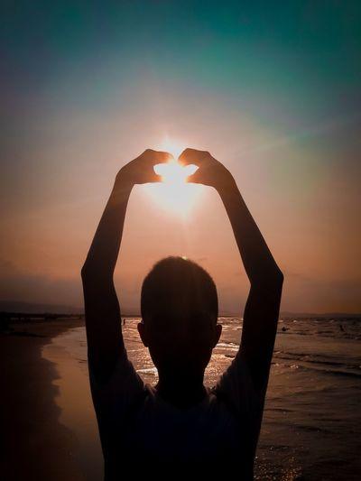 Silhouette man making heart shape against sky during sunset