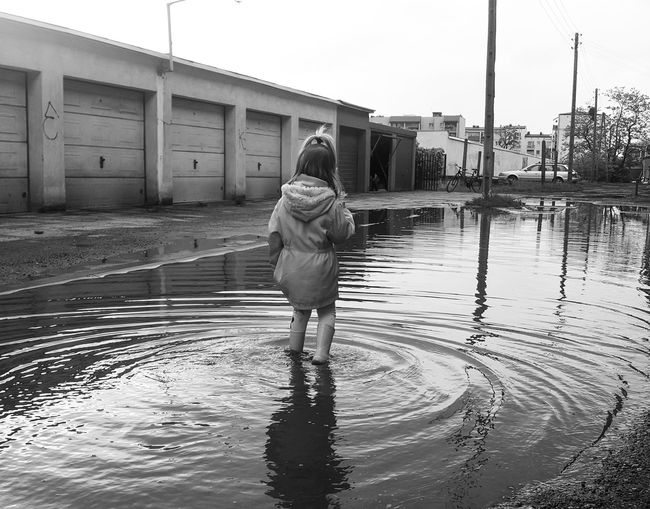 Rear view of girl standing in puddle against sky