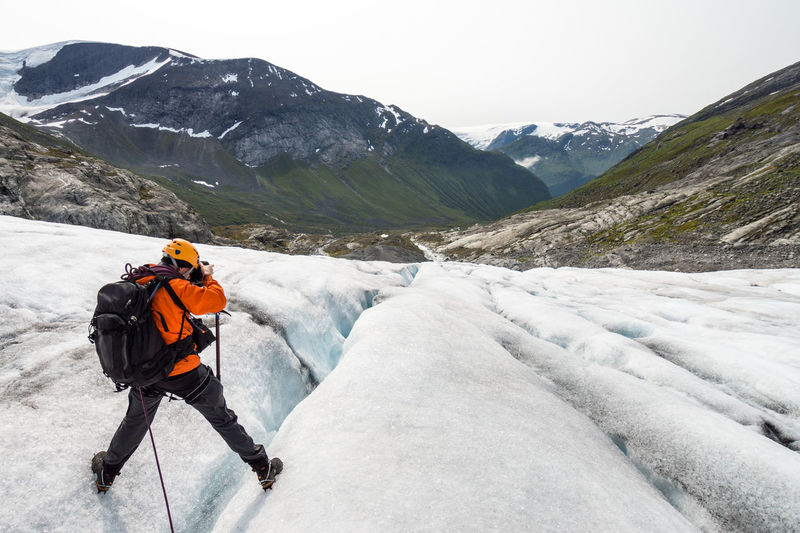 Man photographing while standing on glacier against mountains