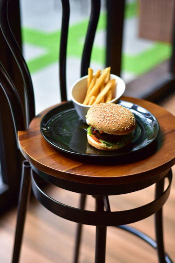 Burger With French Fries In Plate On Wooden Chair
