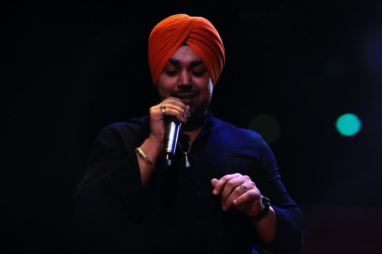 Low Angle View Of Singer Singing Against Black Background