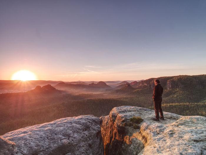 Hiker watch sunrise in rocky misty landscape. travel alone. man standing on mountain summit