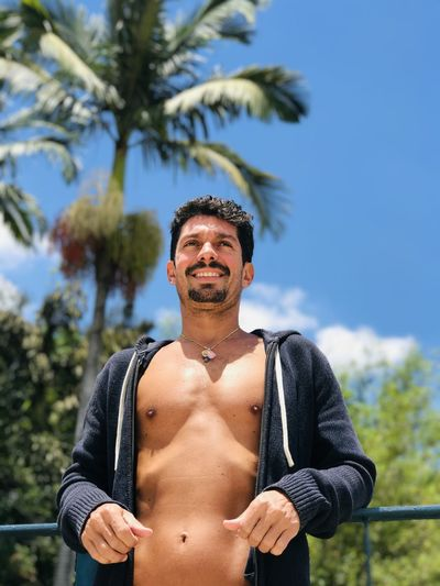Portrait of shirtless man standing against sky