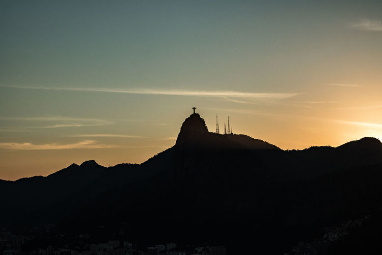 Distant view of christ the redeemer against sky during sunset
