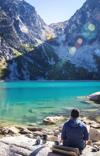 Rear View Of Woman Sitting On Mat At Rock By Colchuck Lake And Mountains