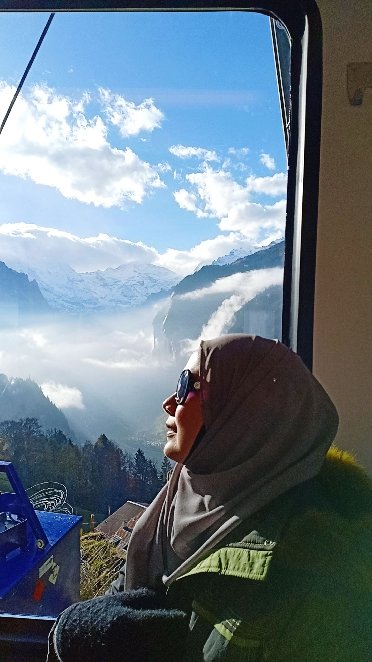cloud - sky, mountain, one person, leisure activity, sky, real people, lifestyles, day, nature, window, sitting, beauty in nature, mountain range, young adult, mode of transportation, sunlight, transportation, portrait, vehicle interior, outdoors