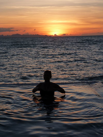 Silhouette man swimming in sea against sky during sunset