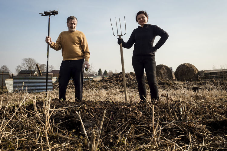 Man and woman with rake and pitchfork work in the field