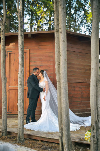 Wedding Couple Kissing While Standing By Built Structure