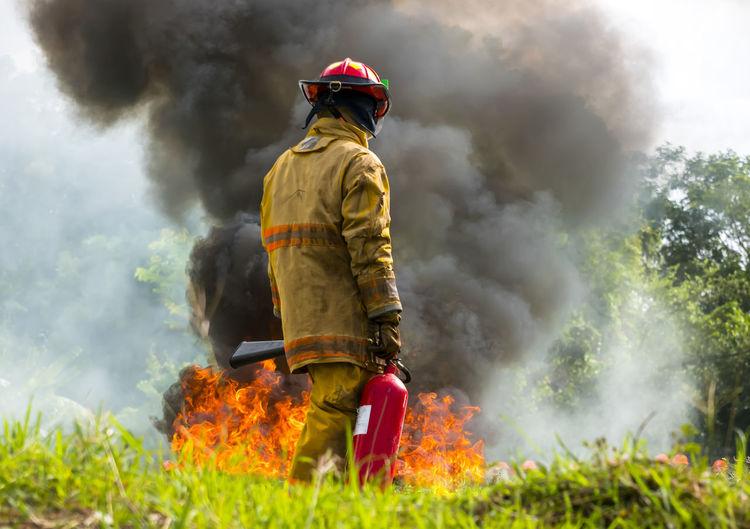 Rear view of man walking by fire