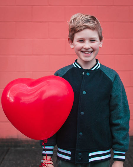 Portrait of smiling boy holding balloon while standing against red wall