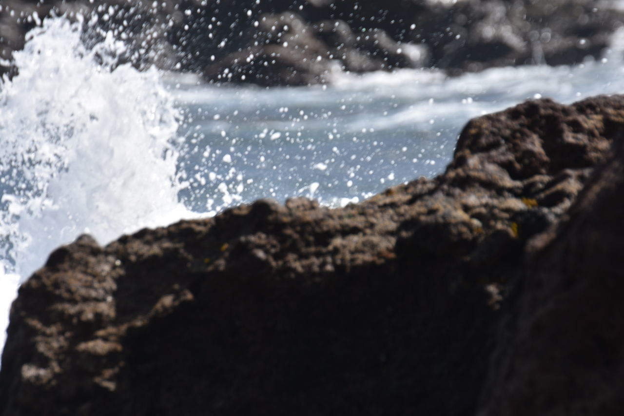 water, sea, motion, rock - object, rock, nature, no people, beauty in nature, solid, splashing, wave, land, outdoors, day, rock formation, aquatic sport, sport, focus on foreground, scenics - nature, power in nature, breaking