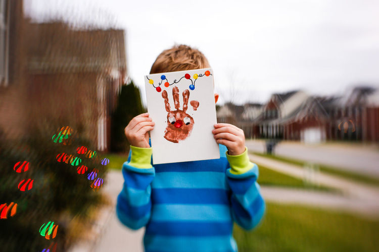 Young Child Holding Hand Print Christmas Art Childhood Child One Person Outdoors Obscured Face Christmas Handprint Handprint Ar Hand Print Christmas Around The World Christmas Lights Christmas Decoration Child's Art Hand Print Art Boy