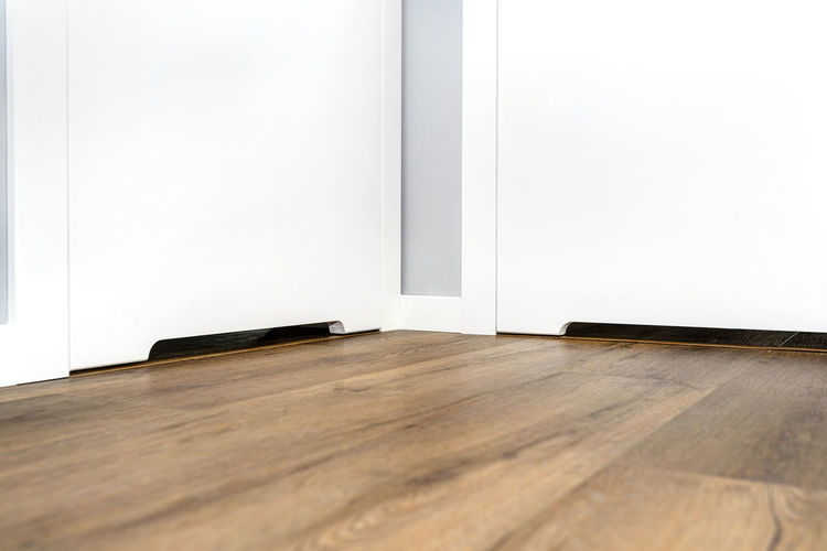 Surface level of wooden floor against white wall