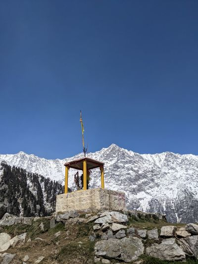 Cross on snowcapped mountains against clear blue sky