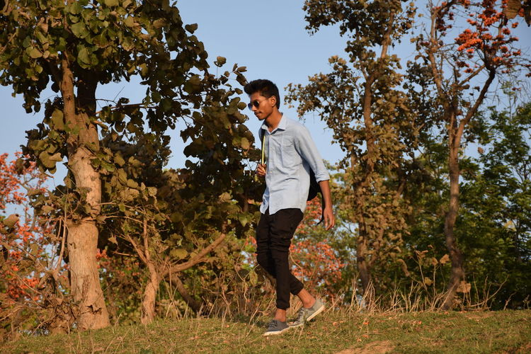 Side view of young man walking on field against trees
