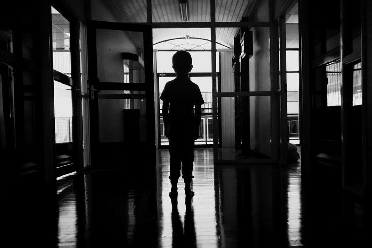 Rear view of silhouette man standing in corridor of building
