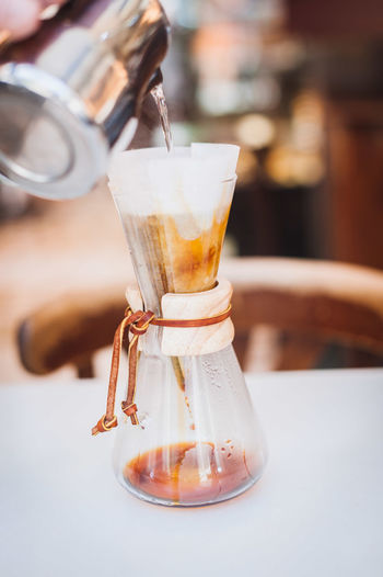 Metal container pouring water in coffee filter on table