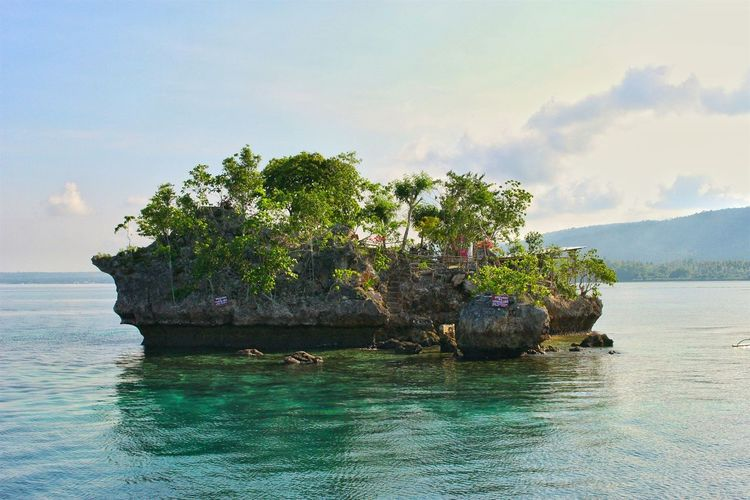 Rock formation at wishing island against sky