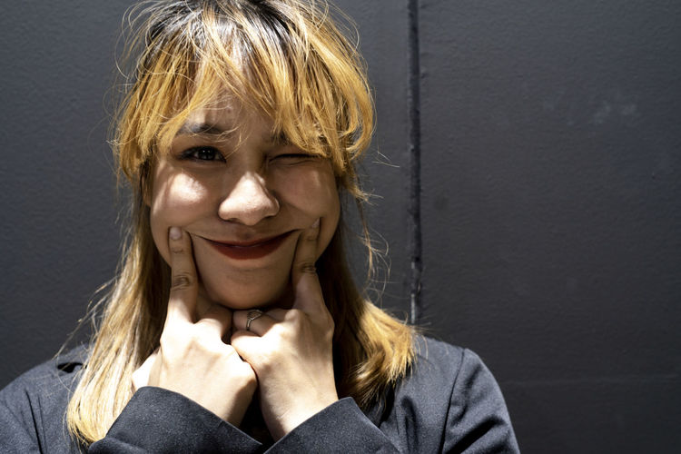 Close-up portrait of smiling businesswoman against wall