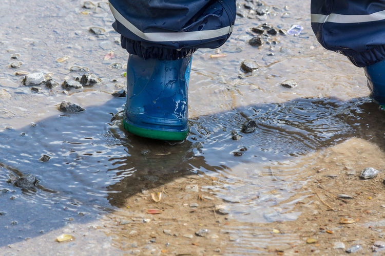 Child with blue rubber boots in a puddle. close up view Boots Drops Of Water Jump; Puddle Rain Adult Adults Only Bubbly Close-up Day Human Body Part Human Leg Low Section One Man Only One Person Only Men Outdoors People Real People Rubber Boots Water