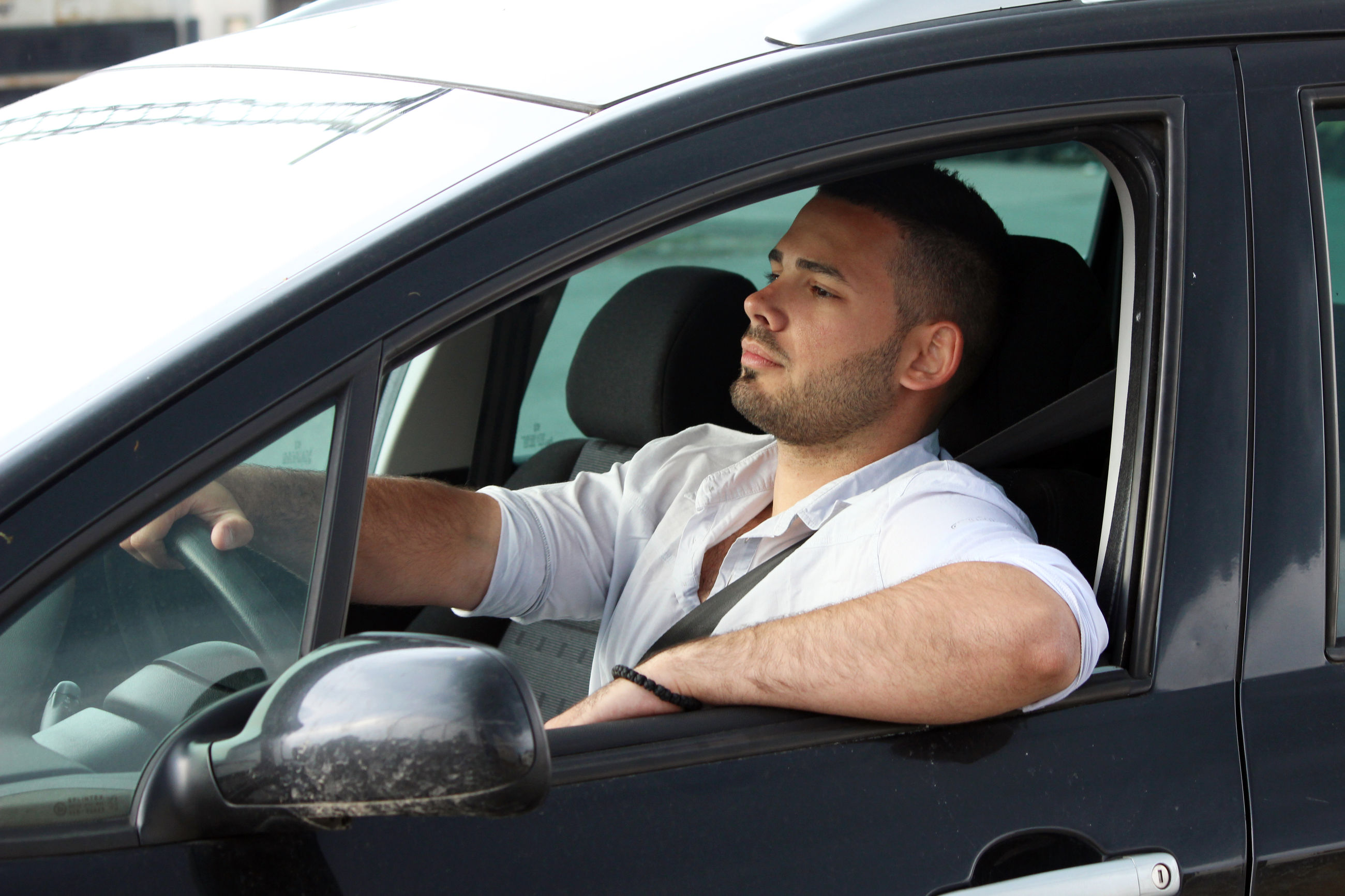 YOUNG MAN LOOKING AT CAMERA WHILE SITTING IN CAR