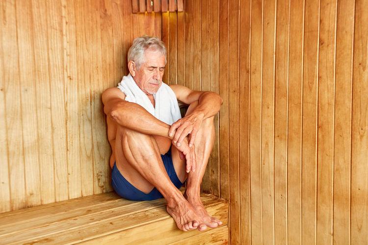 Full length of man sitting on wooden floor