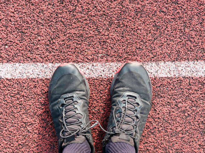 Feet in sneakers stand near the starting line on the red asphalt. bounding line