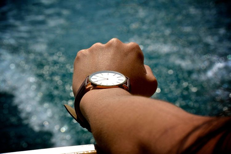 Cropped hand of person wearing wristwatch