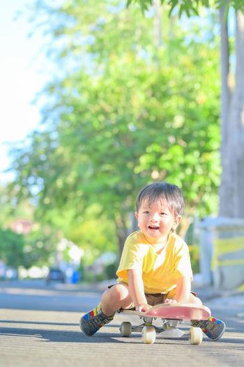 Cute boy sitting on toy against blurred background