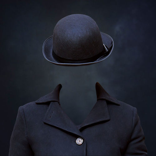 Digital Composite Image Of Invisible Man Wearing Hat Against Black Background
