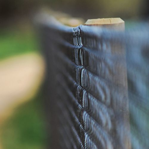 Close-up of chainlink fence by wooden post