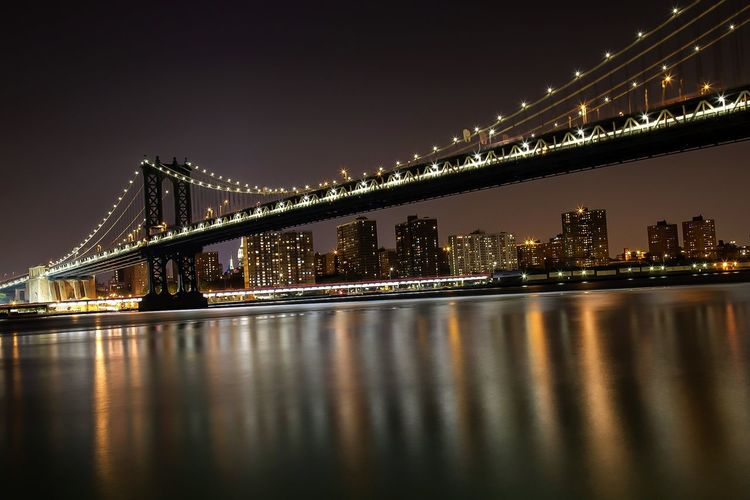 Illuminated manhattan bridge over east river against sky at night