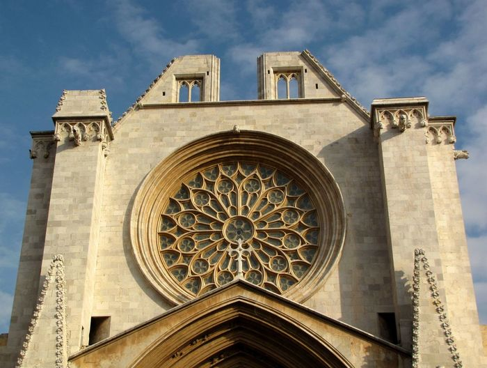 Low Angle View Of Rose Window At Tarragona Cathedral Against Sky