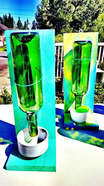 Green Color No People Sunlight Close-up Tree Wine Bottle Bird Feeder Artsy Crafts Crafty Reflective Glass Colored Glass Colorful Design Color Reflection Yellow Blue Blue Sky Aqua Aquamarine Green Glass Green Glass Bottle Wine Not Paint The Town Yellow