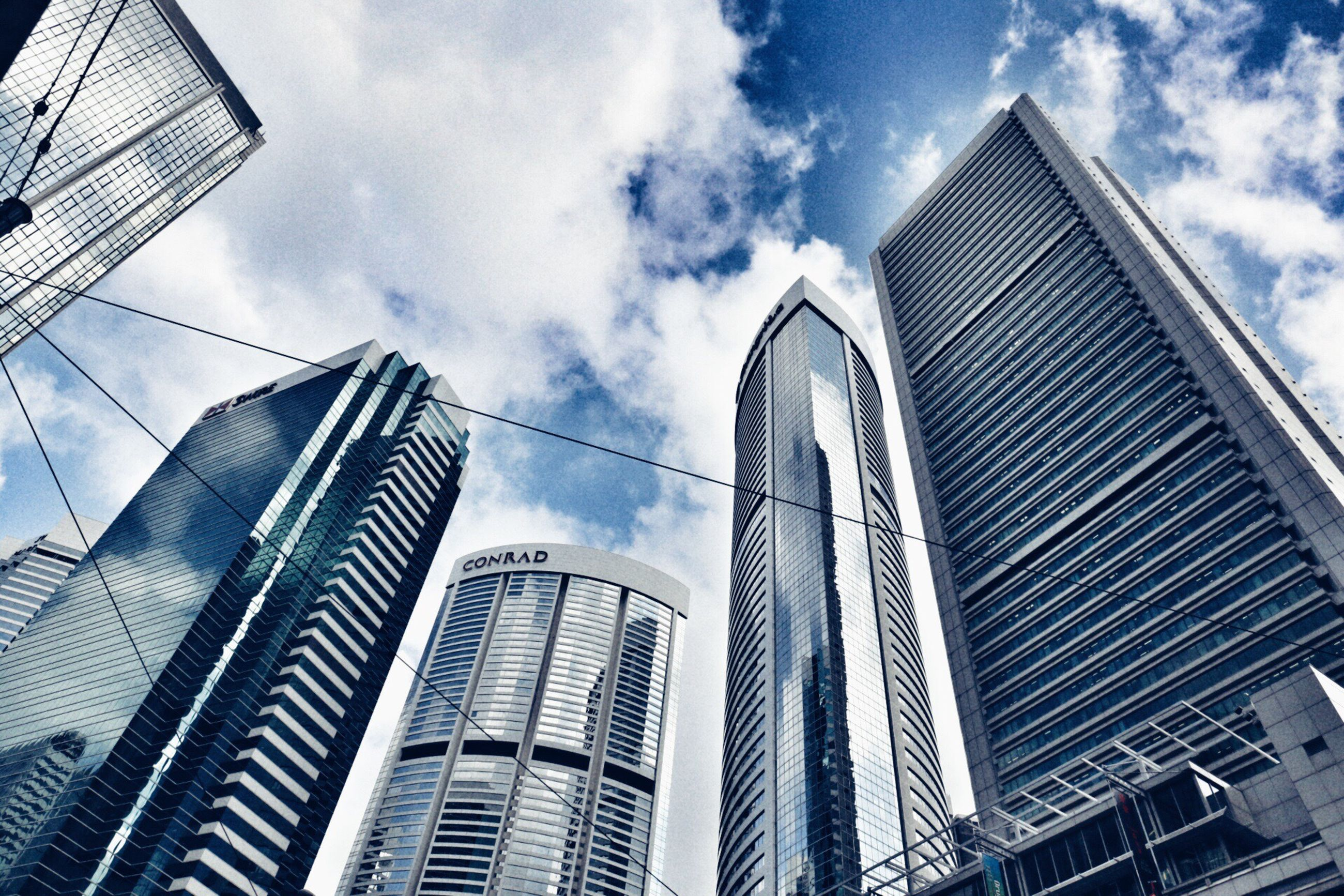 low angle view, architecture, built structure, skyscraper, tall - high, building exterior, tower, city, sky, office building, modern, cloud, tall, outdoors, spire, cloud - sky, building story, growth, day, capital cities, blue, financial district, urban skyline, no people