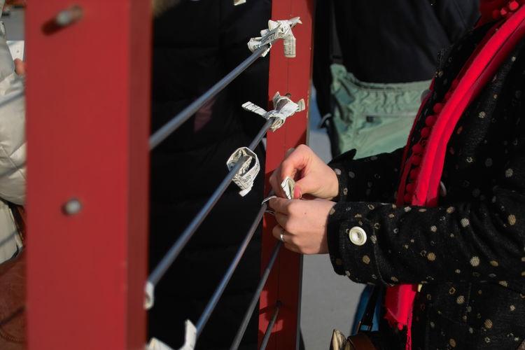Close-up of tying wish on railing