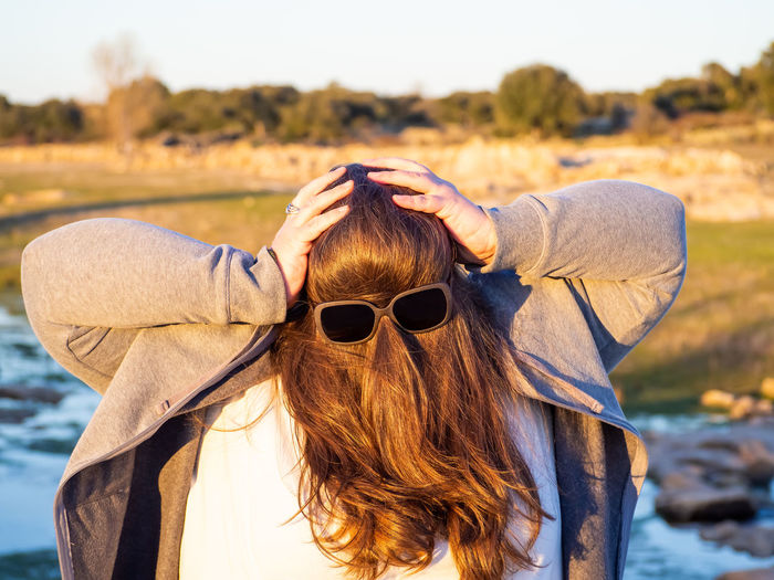 Woman with obscured face wearing sunglasses on hair