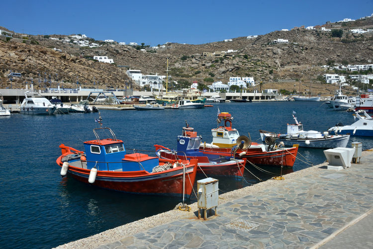 panoramic view of Mykonos harbor with white buildings and fisherman colored typical boats moored. Nautical Vessel Transportation Water Moored Mode Of Transportation Mountain Architecture Nature Day Sea Harbor Sky No People Sunlight Building Exterior Built Structure Clear Sky Outdoors City Sailboat Anchored Port Fishing Boat Marina Luxury Mykonos,Greece Colored Boats Tourism Bay Travel Destinations Panoramic View Pier Dock