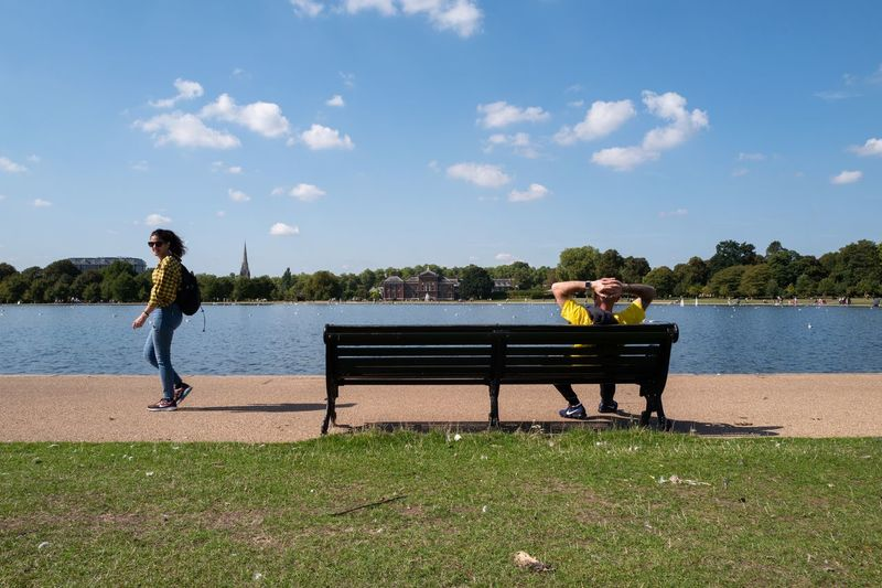 Woman sitting on bench by lake against sky