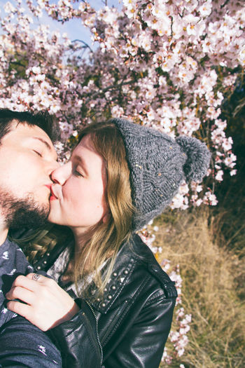 Adult Bonding Couple - Relationship Emotion Eyes Closed  Leisure Activity Lifestyles Love Nature Outdoors Plant Positive Emotion Real People Togetherness Tree Two People Women Young Adult Young Men Young Women
