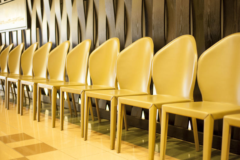 Row of empty golden chairs waiting for some very important guests. 43 Golden Moments Absence Arrangement Bright Business Chairs Close-up Decoration Empty Furniture Gold Golden In A Row Indoors  Leather No People Quiet Repetition Row Seat Side By Side Still Life Vibrant Waiting Yellow