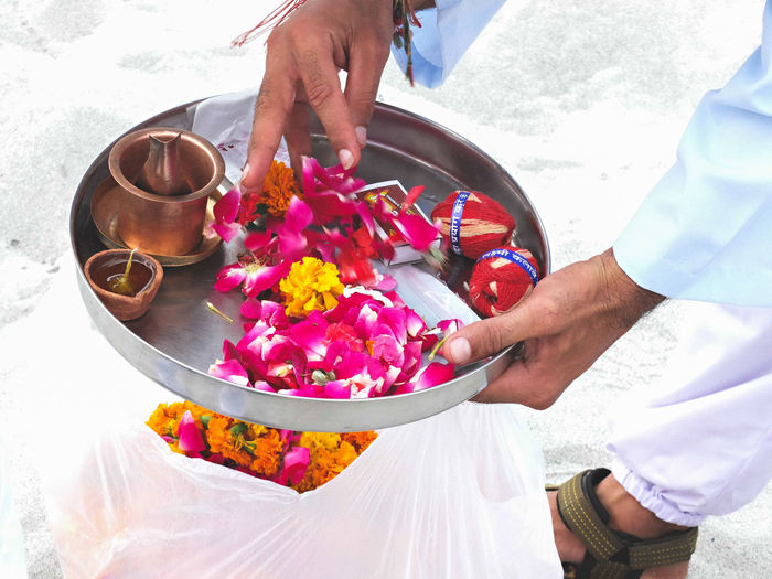 Low Section Of Man Holding Plate With Flowers And Diya