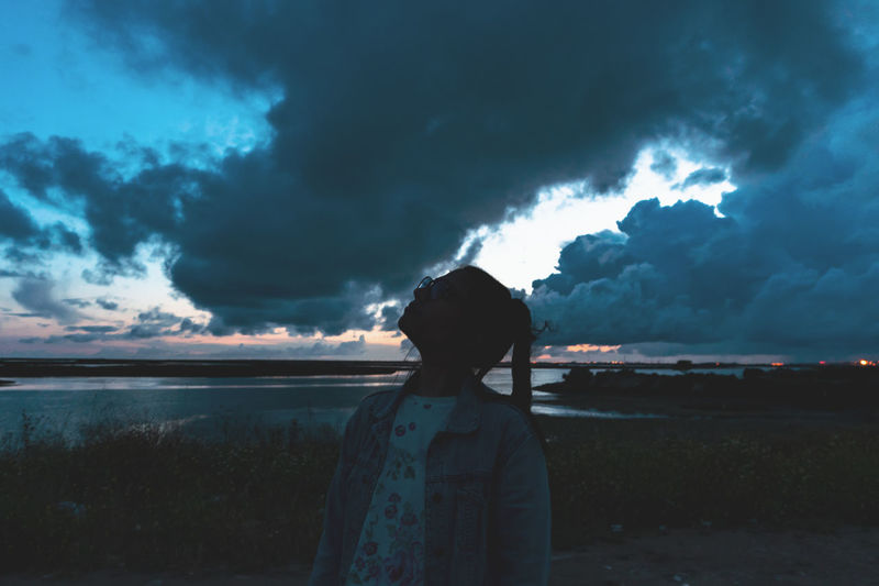 Beauty In Nature Cloud - Sky Dusk Land Leisure Activity Lifestyles Looking At View Nature One Person Outdoors Real People Rear View Scenics - Nature Sky Standing Storm Storm Cloud Sunset Tranquil Scene Waist Up Water The Great Outdoors - 2018 EyeEm Awards