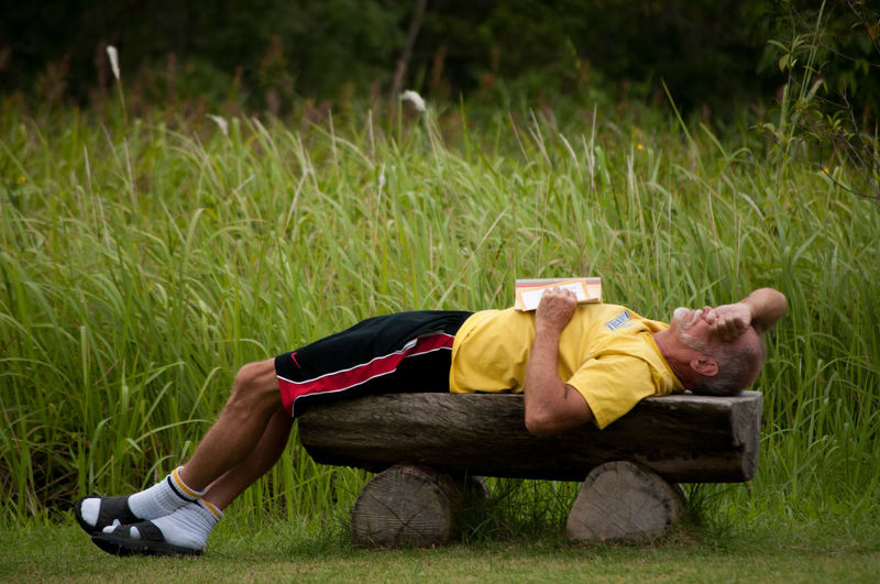 Side view of a man lying on bench against grass
