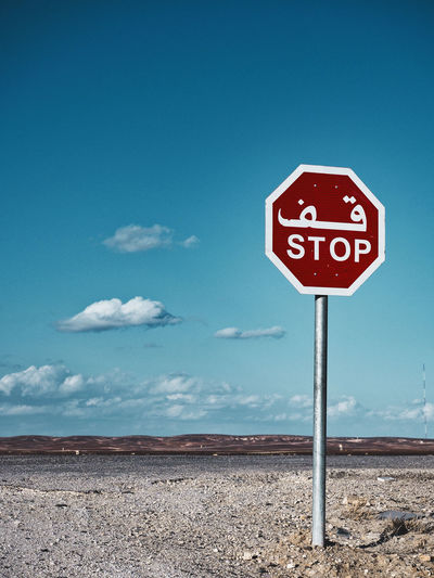 Stop street sign in english and arabic language in non urban area