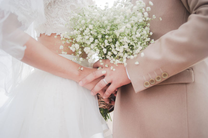 Midsection of bride and bridegroom holding bouquet