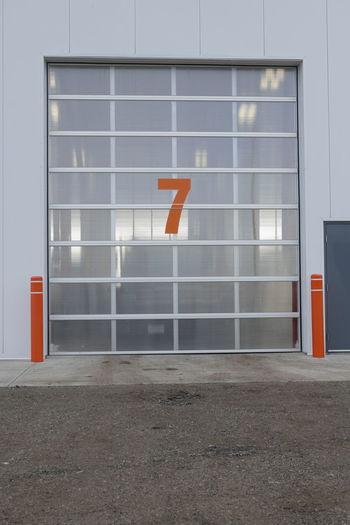 Door Number Seven. 7 Building Exterior Day Loading Door No People Overhead Door Red Number See-through Seven