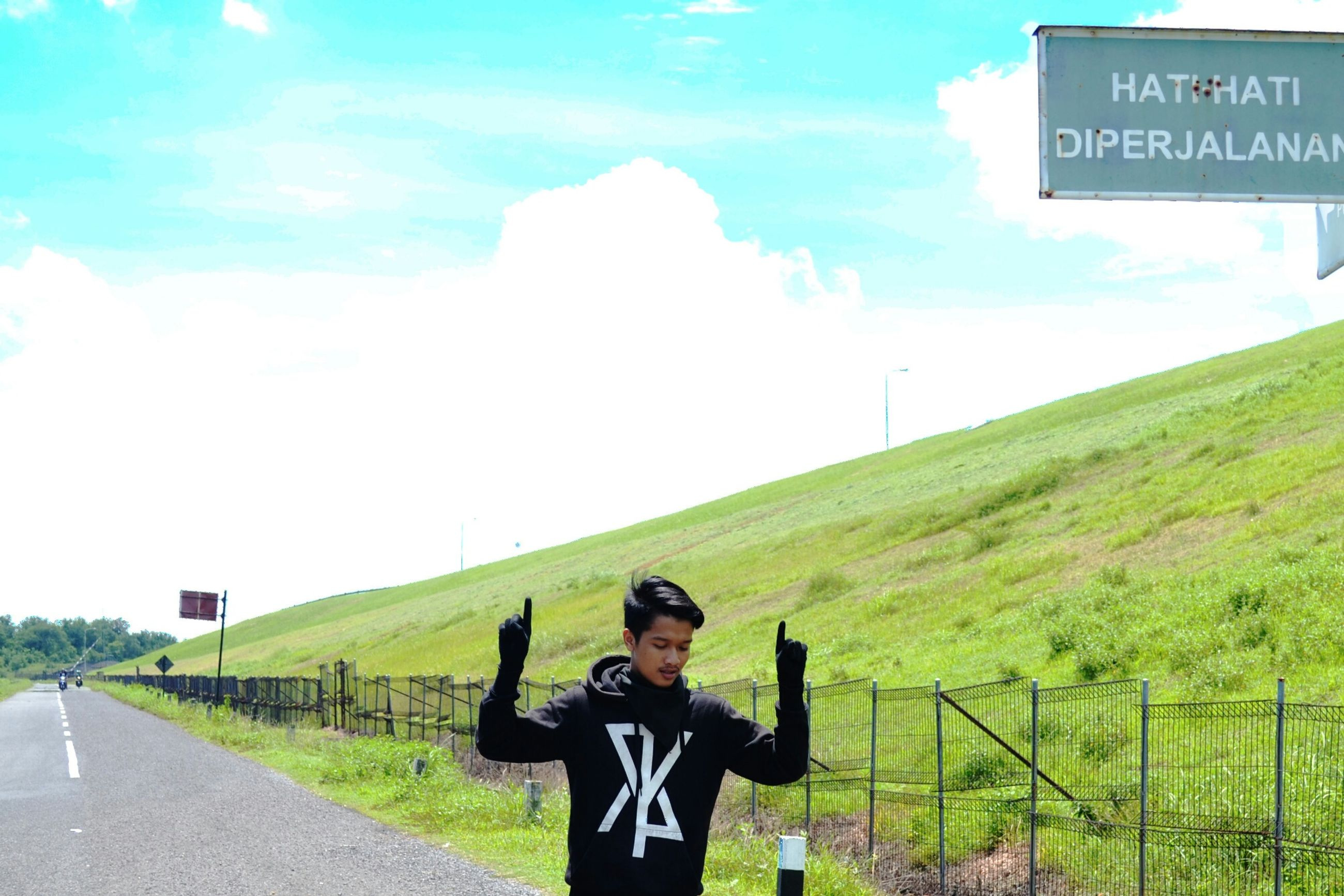 lifestyles, leisure activity, sky, standing, casual clothing, young adult, grass, person, young men, field, full length, road, mountain, day, front view, three quarter length, landscape, looking at camera