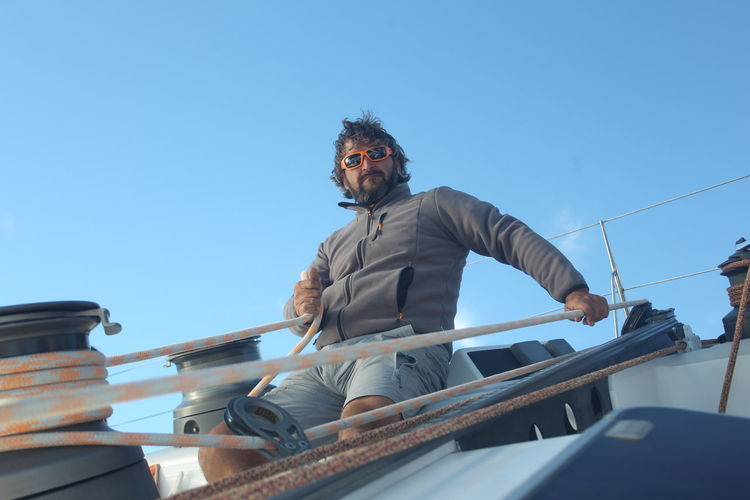 Man pulling rope on sailboat against blue sky